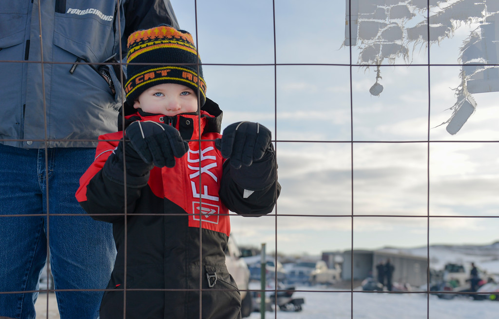 Justin Sheely | The Sheridan Press<br /> Four-year-old Tucker Low of Priest River, Idaho, look onto the track as drivers test their sleds during the snowmobile racing event at Sheridan Speedway Saturday, Jan. 27, 2018. This was the first time Sheridan hosted the Extreme Mountain Racing circuit.
