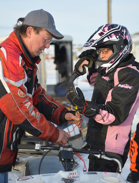Justin Sheely | The Sheridan Press<br /> Tom Kekich, left, puts a safety tether on driver Chalis Bremkamp as they test their machines during the snowmobile racing event at Sheridan Speedway Saturday, Jan. 27, 2018. This was the first time Sheridan hosted the Extreme Mountain Racing circuit.