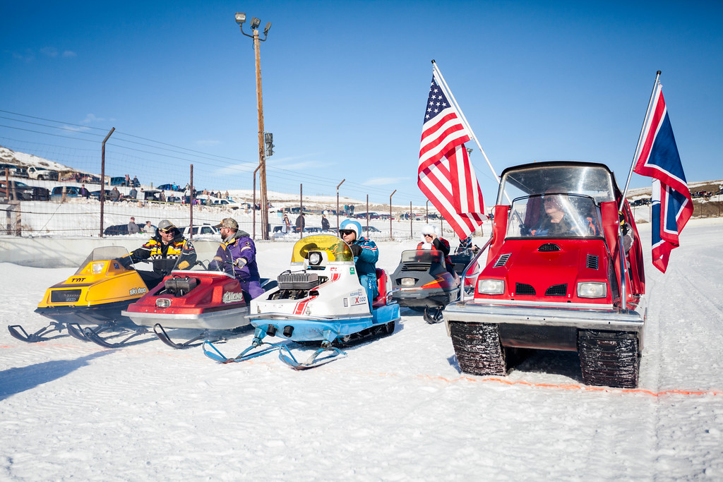 Tibby McDowell | The Sheridan Press<br /> <br /> A group of vintage sled riders parade around the track with flags during the X-Treme Mountain Racing snommobile races at Sheridan Speedway Saturday Jan. 27, 2018.