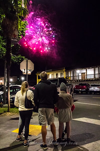 A family watches the fireworks over the barracks and Tuscano Hotel in downtown Sonoma.
