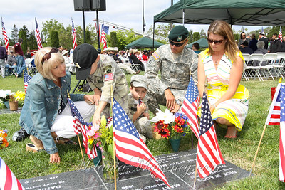 Laurie Norman, along with her daughter Colleen and her husband Col. Robert Marchi, help her grandsons, Liam and Cooper, put flowers on her son Captain Kevin Norman's grave.