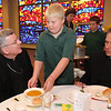 Alex Moeller, center, a fifth-grader at Highland Catholic School in St. Paul, serves a bowl of Classic Butternut Squash Soup to Archbishop John Nienstedt Oct. 13 during the school-sponsored Fall Harvest Soup Luncheon, which was served at Lumen Christi Catholic Community next door. Archbishop Nienstedt said Mass for the school children, then sat down for lunch with the pastor of Lumen Christi, Father Paul Feela, right. Students made the soup and other menu items (apple cake and herb butter) with vegetables grown on school grounds by students belonging to the Hi-C Garden Club. Then, in addition to Archbishop Nienstedt, they invited seniors from the parish to enjoy the food they prepared.