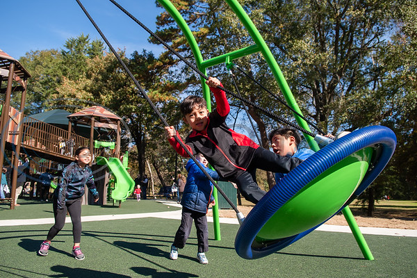 Seven-year-old Isaiah Rosales (wearing red) and his nephew Ares Rosales, 6, ride a giant swing during the grand opening of Southside Park playground, an inclusive park where children of all abilities can play, Saturday, Nov. 16, 2019, in Tyler. (Cara Campbell/Tyler Morning Telegraph)