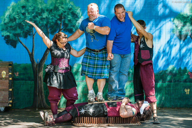 A performer for the Pickled Brothers Sword Swallowing,  Fire Eating, Juggling Etc. laying on a bed of nails while two volunteers stand on top of him on a board. This was part of a performance on July 5, 2014 as part of the annual 2014 Kentucky Renaissance Fair in Eminence, Ky.