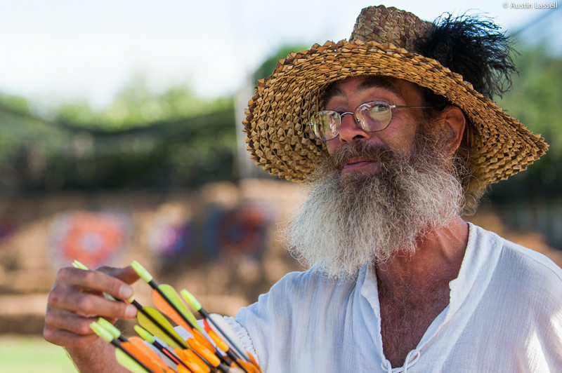 A worker sorting arrows before handing them out at a pay-to-shoot arrow stand. The arrow shooting stand allowed participants to pay to shoot arrows at targets painted on hay bales. This photo was taken on July 5, 2014, during the annual 2014 Kentucky Renaissance Fair in Eminence, Ky.