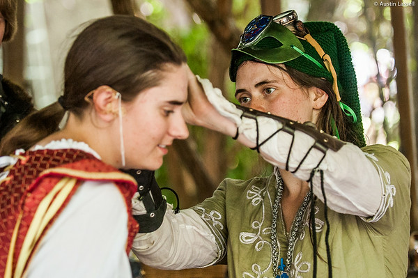 A young participant receives assistance with an ear ring purchased from the owner of a shop seen on right on July 5, 2014, during the annual 2014 Kentucky Renaissance Fair in Eminence, Ky.