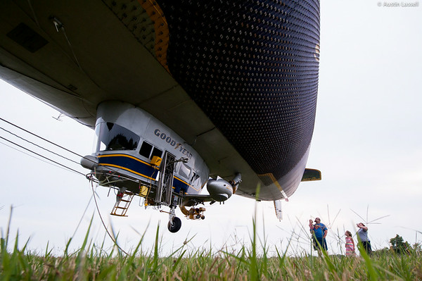 The Goodyear blimp is no small feat. At 50 feet in diameter and 192 feet in length, Goodyear's Spirit of Innovation blimp, tail number N2A, houses some 200,000 cubic feet of helium, making the blimp itself a repository of a small fortune of the natural resource. Although the blimp weighs over 10,000 pounds empty, the addition of the lighter than air helium reduces the blimp to weighing only a few hundred pounds. In order to raise and lower the blimp, large rubber bladders of air are inflated or deflated inside the blimp. This action changes the density of the blimp relative to the surrounding air, making the blimp more or less buoyant.