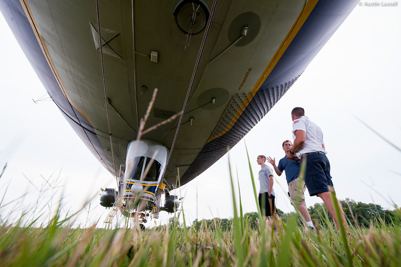 Local Louisville, Kentucky pilot Mark speaks with a mechanic overlooking Goodyear's Spirit of Innovation blimp, tail number N2A. As the blimp is not designed to truly land, it can be damaged should it rest its full weight on the ground. As such ground support crew members are provided around the clock, 24/7, to ensure that the blimp is in proper operating order. In this photo the blimp was in Louisville, Kentucky in order to provide coverage of the 2014 PGA Championships at the Valhalla Golf Club in Louisville, Kentucky.