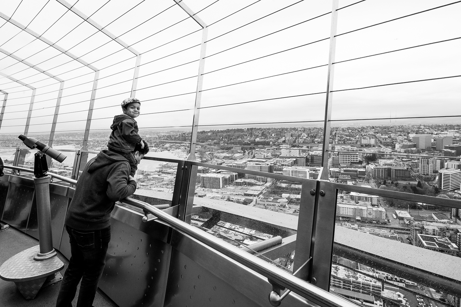 Perched higher than most, even atop the Space Needle in Seattle, WA, a young man smirks for the camera on a rainy day in March.