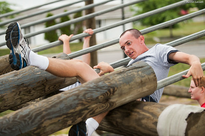 A 4th Company candidate overcoming an obstacle during obstacle course training at SUNY Maritime College on July 16th, 2014. In this obstacle candidates must straddle down two metal bars.