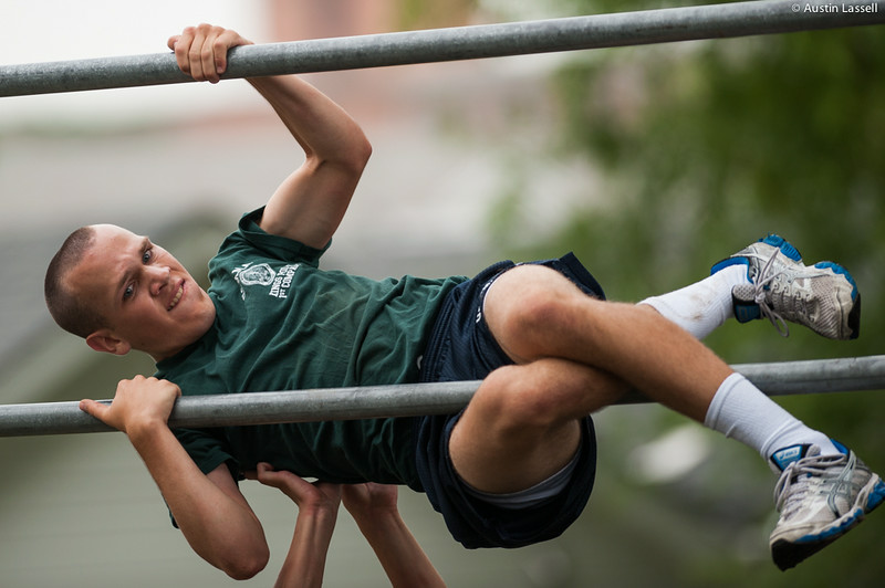 A 1st Company Platoon 102 candidate struggling to overcome an obstacle during obstacle course training at SUNY Maritime College on July 14th, 2014. On this obstacle candidates must get their body overtop the two bar seen quickly and safely out of contact with the ground. This obstacle is challenging in that it is difficult to carry out quickly and safely. If several efforts are not successful, the candidate may have the assistance of their obstacle course teammate.