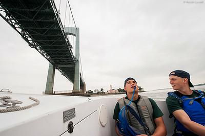 A 1st Company Platoon 102 candidate looking up as he passes beneath the Throggs Neck Bridge while riding on a Launcher headed to obstacle course training on July 14th,  2014. This candidate, and his other fellow candidates, are being led by Midshipman Andrew 3rd Classman.