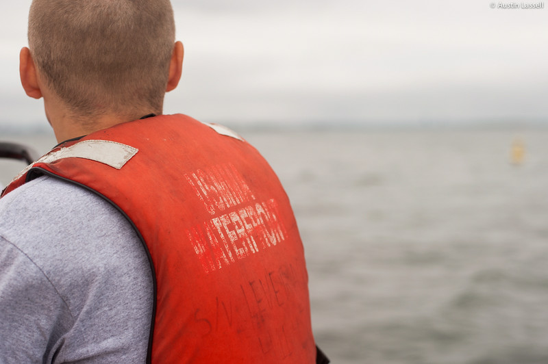 """A closeup of the life jacket of a 4th Company candidate that reads """"USMMA Waterfront"""" who is riding on a Whaler being piloted by midshipman William Lassell 3rd Classman during small boats class on July 16th, 2014. """"Waterfront"""" at the Merchant Marine Academy refers to the docks that house Merchant Marine's boats in Hague Basin. During each summer's  Indoctrination of each new class, the Waterfront provides candidates with basic training concerning small boats and larger vessels. As compared to other Indoctrination training, Waterfront training is considered to be a nice change of pace, as while it is still full or responsibility, it includes the excitement of getting out onto open water."""