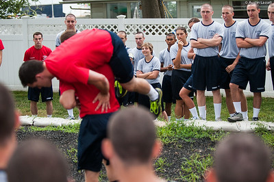 Indoctrination officers teach 4th Company candidates the proper carrying technique for carrying a fellow mariner as part of obstacle course training on July 16th, 2014.