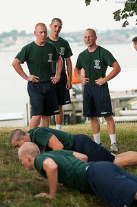 """1st Company Platoon 102 candidates overcoming an obstacle during obstacle course training while fellow candidates look on at SUNY Maritime College on July 14th, 2014. This is a simple workout portion of the course that takes place at the end of the course. The workout being performed is a """"burpie"""", a pushup followed by a jumping jack, and must be done in several repetitions."""