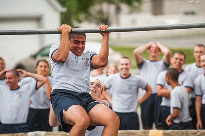 4th Company candidates share reactions as a fellow candidate nears closer to overcoming an obstacle during obstacle course training at SUNY Maritime College on July 16th, 2014. On this obstacle candidates must get their body overtop the bar seen without contact with the ground. If several efforts are not successful, the candidate may have the assistance of their obstacle course teammate.