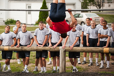 4th Company candidates share mixed reactions as an indoctrination officer demonstrates techniques to overcome an obstacle during obstacle course training on July 16th, 2014. In this obstacle candidates must pass overtop a bar that is above their heads using not support other that the bar.