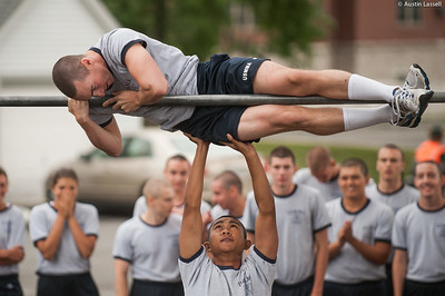 A 4th Company candidate overcoming an obstacle during obstacle course training at SUNY Maritime College on July 16th, 2014. On this obstacle candidates must get their body overtop the bar seen without contact with the ground. If several efforts are not successful, the candidate may have the assistance of their obstacle course teammate.