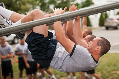 4th Company candidates overcoming an obstacle during obstacle course training at SUNY Maritime College on July 16th, 2014. In this obstacle candidates must straddle down two metal bars.