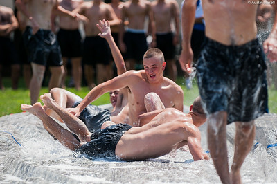 Several candidates fall into one another as they go down the giant slip and slide that is part of the end of Indoctrination Waterfront Games on July 20th, 2014.