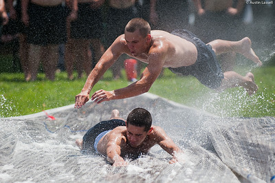 One candidate leaps horizontally onto the slide over another candidate as they  go down the giant slip and slide that is part of the end of Indoctrination Waterfront Games on July 20th, 2014.