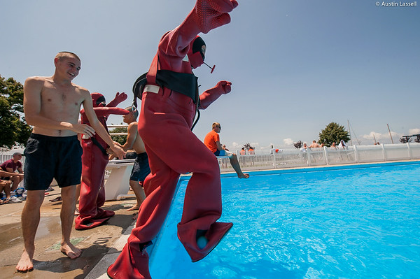 """A USMMA candidate jumps into the pool to begin a lap in a cumbersome survival """"gumby"""" suit as part of a gumby suit relay race during the end of Indoctrination Waterfront Games on July 20th, 2014."""
