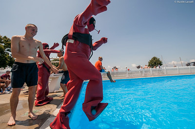 "A USMMA candidate jumps into the pool to begin a lap in a cumbersome survival ""gumby"" suit as part of a gumby suit relay race during the end of Indoctrination Waterfront Games on July 20th, 2014."