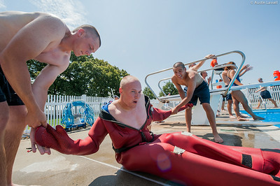 "USMMA candidates help a fellow candidate remove the cumbersome survival ""gumby"" suit after swimming a lap of a gumby suit relay race during the end of Indoctrination Waterfront Games on July 20th, 2014."