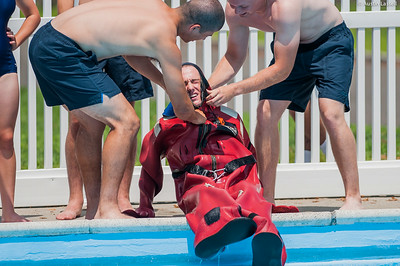 """USMMA candidates help a fellow candidate remove the cumbersome survival """"gumby"""" suit after swimming a lap of a gumby suit relay race during the end of Indoctrination Waterfront Games on July 20th, 2014."""