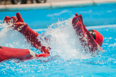 "A USMMA candidate swims as fast as possible in a cumbersome survival ""gumby"" suit as part of a gumby suit relay race during the end of Indoctrination Waterfront Games on July 20th, 2014."