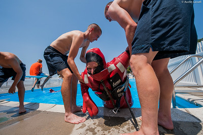 "USMMA candidates help a fellow candidate exit the pool after finishing a lap in a cumbersome survival ""gumby"" suit as part of a gumby suit relay race during the end of Indoctrination Waterfront Games on July 20th, 2014."