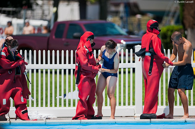 """USMMA candidates help a fellow candidate put on the cumbersome survival """"gumby"""" suit before starting a lap of a gumby suit relay race during the end of Indoctrination Waterfront Games on July 20th, 2014."""