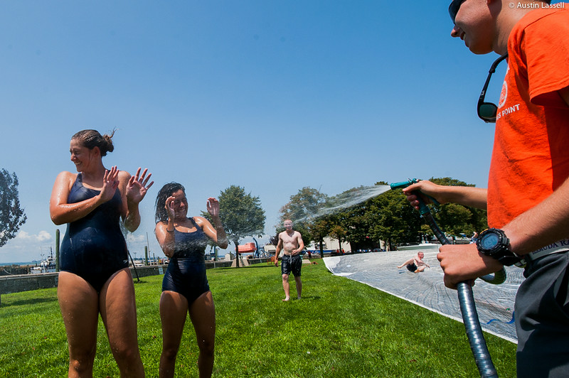 Candidates cringe at cold water as they get soap washed off after going down the giant slip and slide, seen at right, that is part of the end of Indoctrination Waterfront Games on July 20th, 2014.