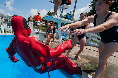 """A USMMA candidate gets pushed backwards into the pool to begin a lap in a cumbersome survival """"gumby"""" suit as part of a gumby suit relay race during the end of Indoctrination Waterfront Games on July 20th, 2014."""