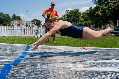 A candidate excitedly leaps horizontally onto the giant slip and slide that is part of the end of Indoctrination Waterfront Games on July 20th, 2014.