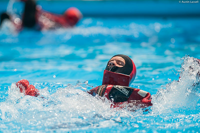 """A USMMA candidate swims as fast as possible in a cumbersome survival """"gumby"""" suit as part of a gumby suit relay race during the end of Indoctrination Waterfront Games on July 20th, 2014."""