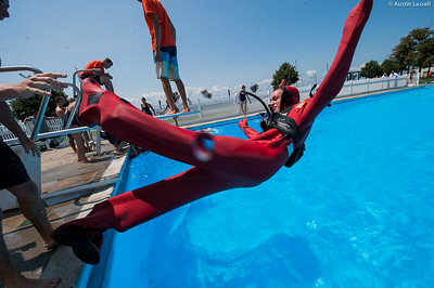 "A USMMA candidate leaps backwards into the pool to begin a lap in a cumbersome survival ""gumby"" suit as part of a gumby suit relay race during the end of Indoctrination Waterfront Games on July 20th, 2014."
