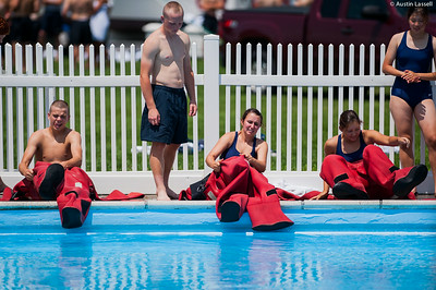 """USMMA candidates attempt to put on the cumbersome survival """"gumby"""" suit before starting a lap of a gumby suit relay race during the end of Indoctrination Waterfront Games on July 20th, 2014."""