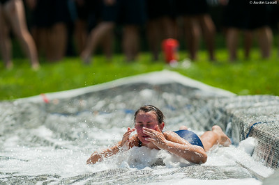 A candidate wipes the soap from her eyes as she goes down the giant slip and slide that is part of the end of Indoctrination Waterfront Games on July 20th, 2014.