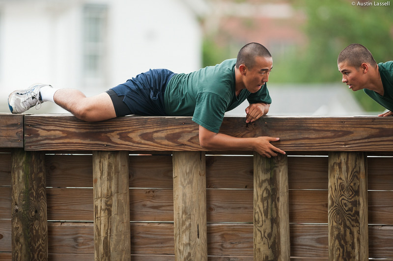 A 1st Company Platoon 102  candidate overcoming an obstacle during obstacle course training at SUNY Maritime College on July 14th, 2014. In this obstacle candidates must passovertop a tall wooden wall that is much taller than standing height of the average candidate while maintaining a low profile.