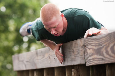 A 1st Company Platoon 102 candidate overcoming an obstacle during obstacle course training at SUNY Maritime College on July 14th, 2014. In this obstacle candidates must pass overtop a tall wooden wall that is much taller than standing height of the average candidate while maintaining a low profile.