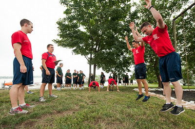 Indoctrination Officer teams at the end of a race during  obstacle course training at SUNY Maritime College on July 14th, 2014. After all the candidate training has completed, a race takes place between two Indoctrination Officer teams. Each team is racing on behalf of a portion of the candidates and the candidates of the winning team will be allowed temporary special privilages.