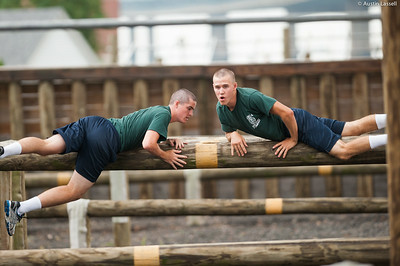 1st Company Platoon 102 candidates overcoming obstacles during obstacle course training at SUNY Maritime College on July 14th, 2014. In these obstacles candidates must quickly get overtop the logs while maintaining a low profile. If several efforts are not successful, the candidate may have the assistance of their obstacle course teammate.