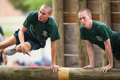 1st Company Platoon 102 candidates overcoming an obstacle during obstacle course training at SUNY Maritime College on July 14th, 2014. On this obstacle candidates must quickly get overtop the log while maintaining a low profile. If several efforts are not successful, the candidate may have the assistance of their obstacle course teammate.