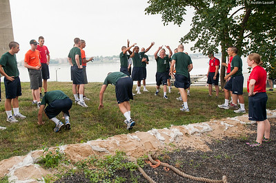 """1st Company Platoon 102 candidates at the end of a race during  obstacle course training at SUNY Maritime College on July 14th, 2014. After all the training has completed, a race takes place between the top candidate teams. In this final portion of the course, the """"burpies"""", it can be seen that the team on right has finished first and won the race."""