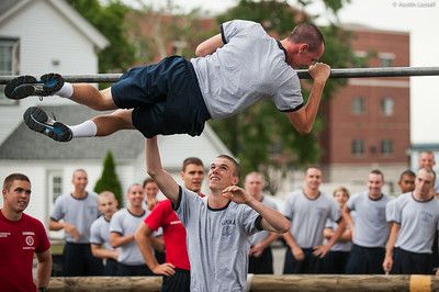 A 4th Company candidate struggling to overcome an obstacle during obstacle course training at SUNY Maritime College on July 16th, 2014. On this obstacle candidates must get their body overtop the bar seen without contact with the ground. If several efforts are not successful, the candidate may have the assistance of their obstacle course teammate.