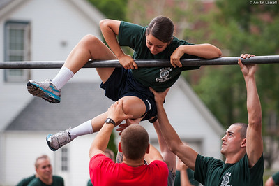 A 1st Company Platoon 102 candidate struggling to overcome an obstacle during obstacle course training at SUNY Maritime College on July 14th, 2014. On this obstacle candidates must get their body overtop the bar seen without contact with the ground. If several efforts are not successful, the candidate may have the assistance of their obstacle course teammate.