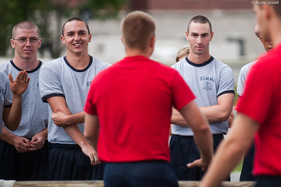 4th Company candidates share mixed reactions as they listen to the instruction of indoctrination officers concerning techniques of overcoming obstacles during obstacle course training on July 16th, 2014.