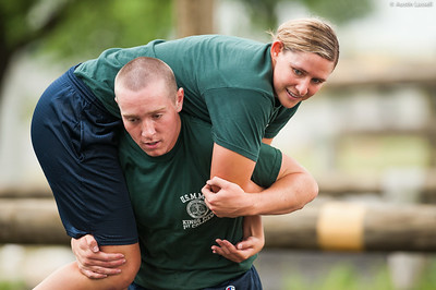 1st Company Platoon 102 candidate Jenna Wetherington being  carried during a man down drill portion of the obstacle course during obstacle course training at SUNY Maritime College on July 14th, 2014. The purpose of this portion of the training is to test the candidate's ability at carrying a downed mariner.