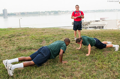 """1st Company Platoon 102 candidates overcoming an obstacle during obstacle course training at SUNY Maritime College on July 14th, 2014. This is a simple workout portion of the course that takes place at the end of the course. The workout being performed is a """"burpie"""", a pushup followed by a jumping jack, and must be done in several repetitions."""